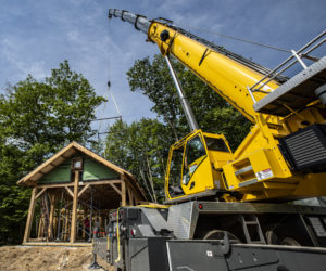 A crane settles the roof in place on an innovative home in Waldoboro on June 5. The house is being designed and built by C.J. Turner, of the Damariscotta-based Alpine Contracting Services LLC. (Bisi Cameron Yee photo)