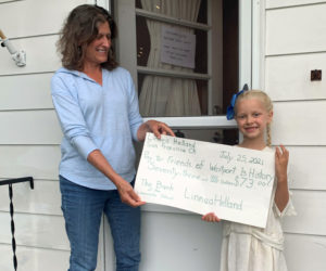 Friends of Westport Island History Committee member Joan Mason-Bradford accepts a donation of $73 from 6-year-old Linnea Helland. Linnea raised the money at her lemonade stand during the town-wide yard sale on Sunday July 18. (Photo courtesy Gaye Wagner)