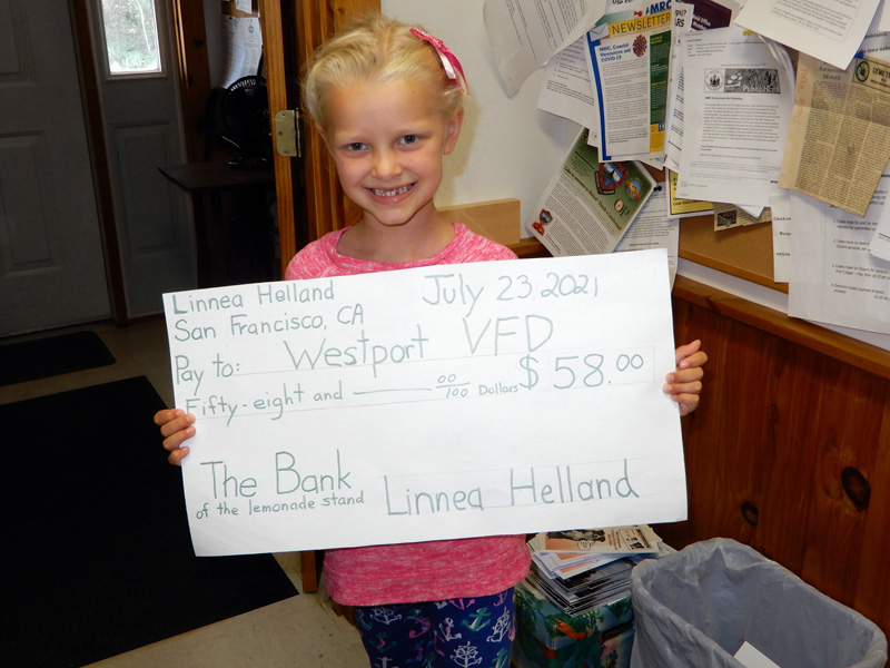 Linnea Helland, 6, holds a check she made to present to the Westport Island Volunteer Fire Department. The check is a portion of the proceeds she gained from her lemonade stand during the town-wide yard sale on July 18. (Photo courtesy Gaye Wagner)