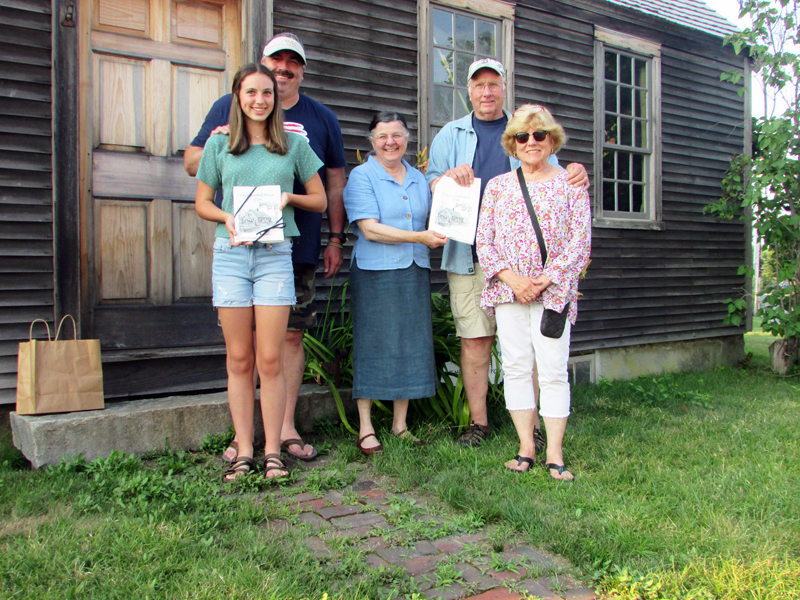 """Louise Miller, of the Chapman-Hall House Stewardship Committee, presents Sandi and Dan Day, their son Justin, and his daughter Zofie, with towels printed with Maurice """"Jake"""" Day's drawing of the Chapman-Hall House, in front of Chapman-Hall House."""