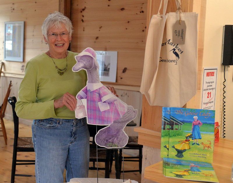"""Jefferson summer resident Sally Kinkade holds up a picture of the concrete goose that belong to her mother Marjorie Bean Scott. Scott and the goose are the subject of a new children's book """"The Goose Lady,"""" by Barbara A. Walsh. (Paula Roberts photo)"""