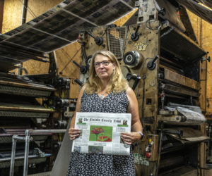 Raye S. Leonard, the new editor of The Lincoln County News, holds an edition of the paper in front of the newspaper presses at Lincoln County Publishing Co. in Newcastle. (Bisi Cameron Yee photo)