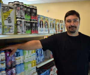 D.J. Foster, owner of Bow Jangles Beverage and Redemption, stands by a selection of Maine beer at his new store. (Evan Houk photo)