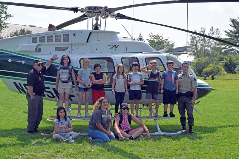 Maine Forest Ranger Pilot Chris Blackie (far left) and Ranger Daniel Welch (far right) stand with campers from the Central Lincoln County YMCA's First Responders Camp. The day marked the end of the first year of the week-long camp at the YMCA. (Nate Poole photo)