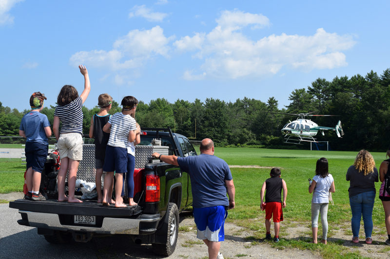 Central Lincoln County YMCA campers wave from Maine Forest Ranger Daniel Welch's tailgate as Ranger Pilot Chris Blackie guides his helicopter away from the Great Salt Bay Community School's football field on Friday, Aug. 6. (Nate Poole photo)
