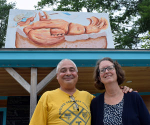 Billy and Barb Ganem, owners of Larson's Lunch Box, stand outside the roadside eatery and the sign handpainted by Newcastle artist Glenn Chadbourne, on Tuesday, Aug. 10. The couple announced in a Facebook post on Sunday, Aug. 8 that they closed the business and will be selling it. (Evan Houk photo)