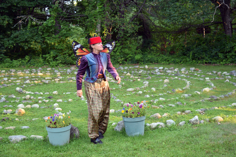 """Laurie Brown as Puck approaches the stage through the entrance of the Edgecomb Community Church's Labyrinth in the Woods, during the Aug. 2 dress rehearsal of """"A Midsummer Night's Dream."""" (Nate Poole photo)"""