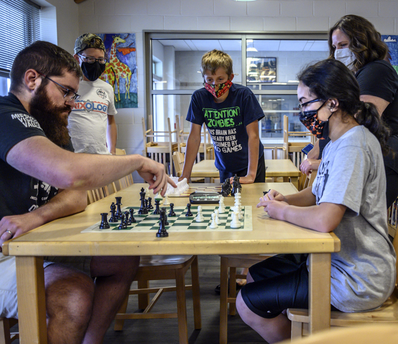 Chess club members observe as Jeff Merckens (left) plays a speed match against Shayla Feng, 11, (right) during a chess club meeting in Jefferson on Tuesday, Aug. 3. Merckens won the match this time, but lost to Pheng in an earlier game. (Bisi Cameron Yee photo)