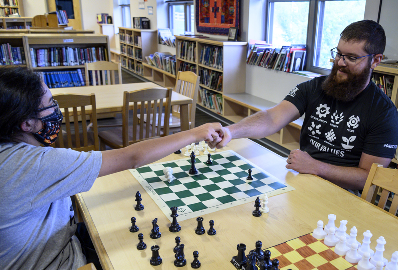 Shayla Pheng, 11, (right) congratulates Jeff Merckens after being checkmated during a chess club meeting in Jefferson on Tuesday, Aug. 3. The white king is tipped over on the board to signify the loss. (Bisi Cameron Yee photo)
