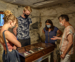 From left: Paisley Stocks, Bastian Zachariassen, Elise Paisley, and docent Christine Hopf-Lovette consider a case of handcuffs at the Old Jail in Wiscasset. Stocks and Paisley are visiting from Mill Valley, Ca., and Zachariassen hails from Denmark. (Bisi Cameron Yee photo)