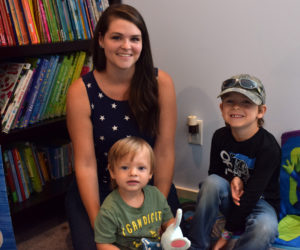 Newcastle resident Emily Krah sits with her two sons-- Raylan, 5, and Jace, one-and-a-half-- in front of a bookshelf at her home on Monday, Aug. 2. Krah has amassed a collection of nearly 600 children's books during her time working as an Usbourne Books & More seller. (Evan Houk photo)