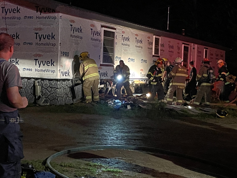 Fire fighters from six area departments peel away foundation material from a home on Hilton Road where a fire was reported Friday, Aug. 13. (Photo by Raye S. Leonard)