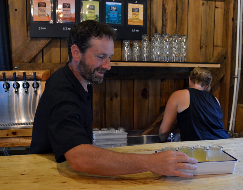 Tin Top Cider Co. co-owner Jon Villeneuve fills a tray with a tasting flight of ciders during the business's soft opening in Alna on Aug. 14. (Maia Zewert photo)