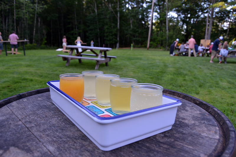 Tin Top Cider Co. in Alna offers flights of its current offerings. The whiskey barrel, now repurposed as a table for the outdoor seating area, is used in the fermentation process of Flow, one of the ciders now on tap. (Maia Zewert photo)