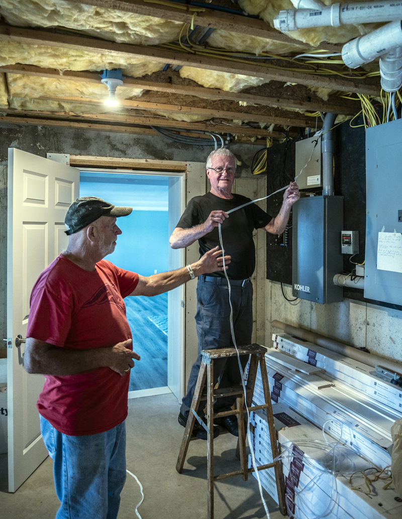 Sam Hafford and Ernie Carroll feed a length of tape from inside a basement through to the exterior of a home in Bremen on Tuesday, Sept. 7. (Bisi Cameron Yee photo)