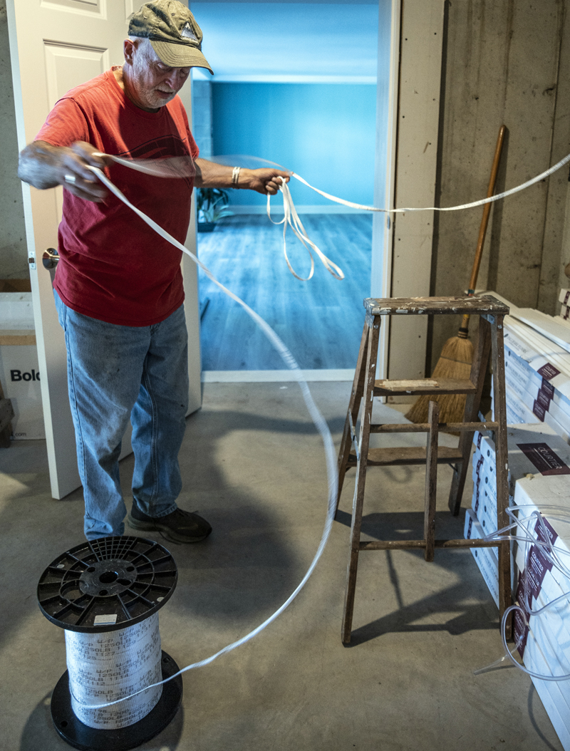 Sam Hafford unspools a length of tape that will eventually guide fiber optic cable into a home in Bremen on Tuesday, Sept. 7. (Bisi Cameron Yee photo)