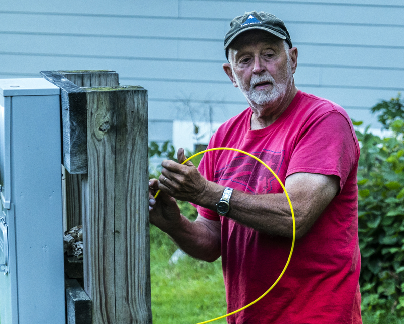 Sam Hafford feeds wire into a conduit at a residence in Bremen on Tuesday, Sept. 7. members of the broadband committee, including Hafford, have volunteered to help prepare sites for connectivity in advance of the final installation of fiber by Tidewater.  (Bisi Cameron Yee photo)