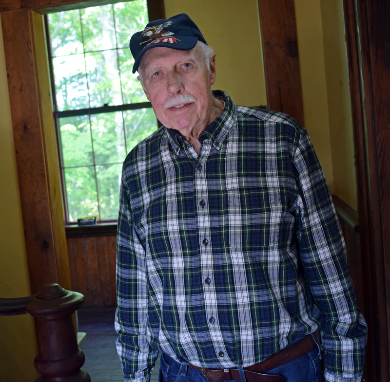 Bill Smith stands in the entryway of the restored Washington School in Round Pond. Smith, who attended the school from 1938 to 1946, helped found the nonprofit Round Pond Schoolhouse Association that worked to restore the 1885 building before it was to be burned as a training exercise for the fire department. (Evan Houk photo)