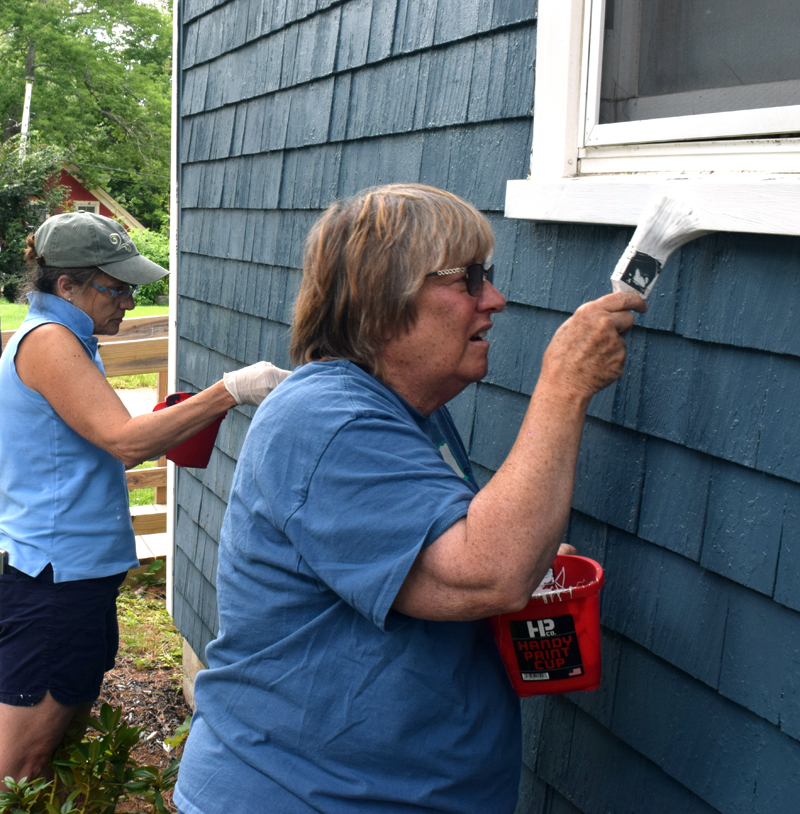 Stepping Stone Housing, Inc. President Marilee Harris and board member Carolyn Neighoff paint a house at Blue Haven, a neighborhood in Damariscotta where the nonprofit owns six homes that are provided as affordable housing options, during Community Cares Day on Saturday, Sept. 11. (Evan Houk photo)