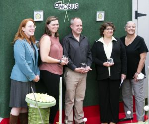 """From left: Rebecca """"Becca"""" Emmons, Emily Huber, Claude Elliott, Cathi Laweryson, and Michaela York pose for photos on an impromptu red carpet at Mobius Inc., in Damariscotta on Sept. 22. The large spool of thread represents the theme of """"the threads we weave"""" that speaks to Mobius' integration into the communities of Lincoln County. (Bisi Cameron Yee photo)"""