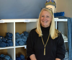 Linda Perry, owner of Sheepscot Harbor Yarns at 74 Main Street in Damariscotta, stands in front of her most popular product, four different shades of hand-dyed indigo yarn that Perry dyes herself at her home on David Island in Edgecomb. (Evan Houk photo)