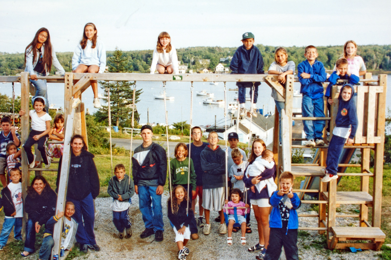 Campers pose for a group photo on a swingset at the Pemaquid Fishermen's Coop during the first 9/11 Famiily Camp at Camp Kieve in 2002. (Photo courtesy Kieve Wavus Education)