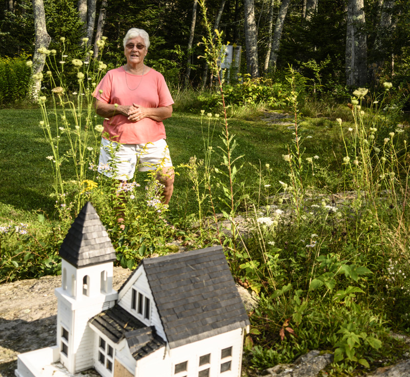 Donna Plummer stands behind a model of the Union Congregational Church on a rock ledge in her front yard in South Bristol. Plummer has been going to the full-sized version of the church since she was three years old.  (Bisi Cameron Yee photo)