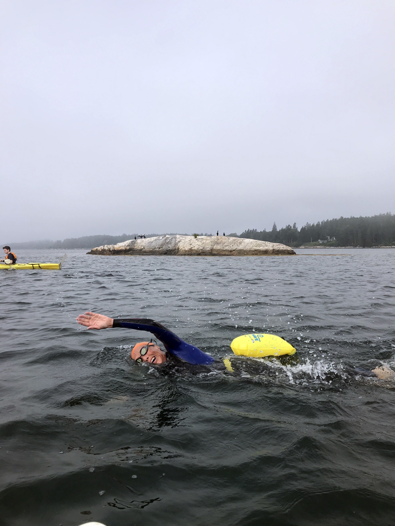 Lorna Fake swimming in Friendship Harbor on Aug. 22 with her safety paddlers in the background for the Cross for LifeLight fundraiser as part of Team Chewonki. (Photo courtesy Lili Pugh)