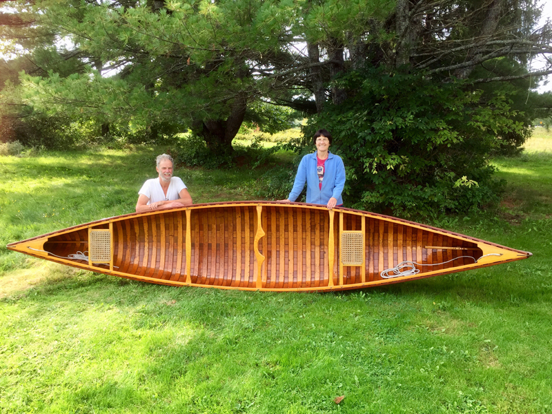 Zip Kellogg and BB Adams with a wooden canoe that they frequently paddle together. Kellogg, a retired librarian, and Adams, a teacher, are both serious paddlers, but met 11 years ago while out dancing. (Photo courtesy Zip Kellogg)