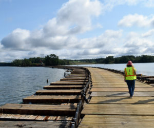 """LCN editor Raye Leonard walks with Central Maine Power Co. Project Manager Nicole Harbaugh and CMP spokesperson Catherine Hartnett on the power company's """"floating road"""" in Great Salt Bay in Newcastle on Friday, Sept. 10. The road was used to access an island for repairs and will be taken out this week. (Evan Houk photo)"""