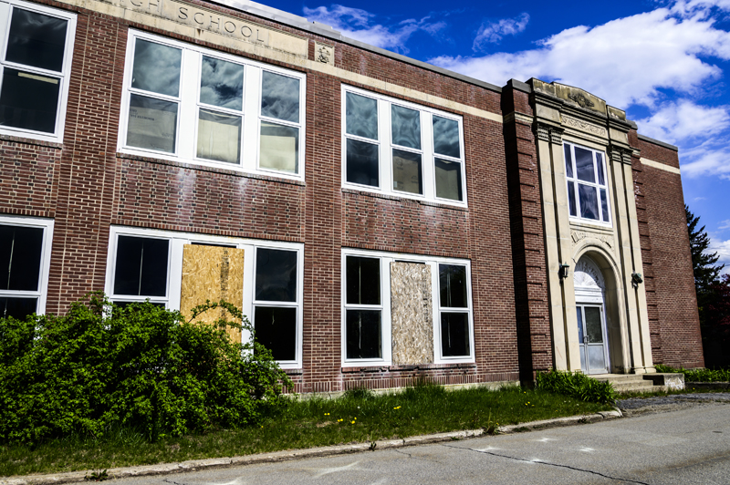 Boards cover broken windows on the front of the A.D. Gray building in Waldoboro on May 14. The brick facade that covers the building has been deemed unstable and the building may need to be demolished. (Bisi Cameron Yee photo, LCN file)