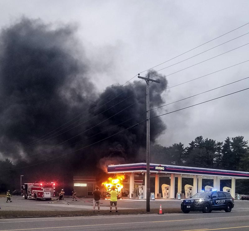 Observers watch as firefighters extinguish a burning camper at the Irving gas station and Circle K in Wiscasset on Sept. 24. The plume of black smoke could be seen from a mile away, according to bystanders. (Bisi Cameron Yee photo)