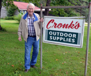 """Oscar Cronk stands by his sign on the Gardner Road. """"Cronk's Outdoor Supplies"""" will be coming down since he recently sold the business, and announced he will retire after nearly 60 years. (Charlotte Boynton photo)"""