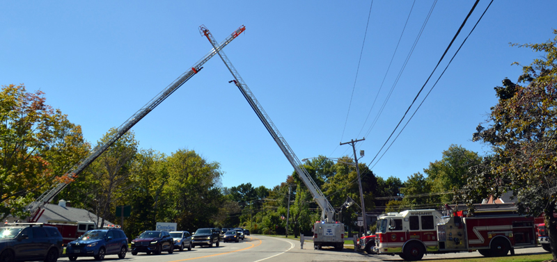 Two of Wiscasset's aerial ladder trucks form a cross over U.S. Route 1 in Wiscasset on Sunday, Sept. 19, during the celebration of life to honor the late Peter Rines. The crossed ladders is a symbol of a bridge to a deceased fireman's next life.  (Charlotte Boynton photo)