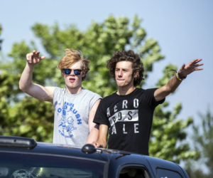 Two Medomak Valley High School seniors wave from a sunroof during a motorcade to celebrate the class of 2021 in Waldoboro on June 6. (Bisi Cameron Yee photo)