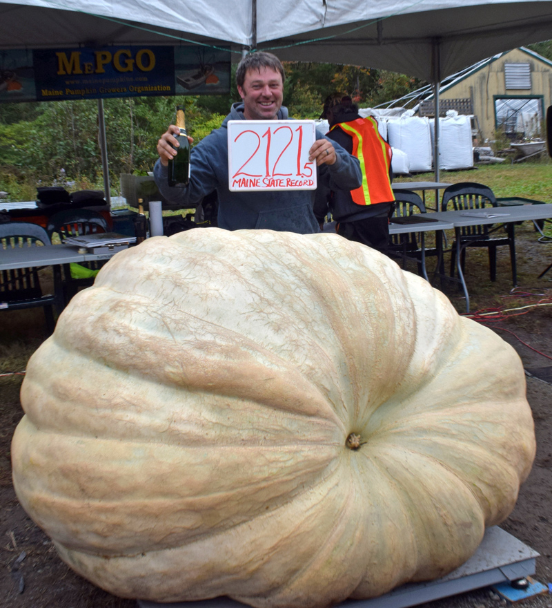 Edwin Pierpont, of Jefferson, poses with his state record giant pumpkin that took first place in the adult giant pumpkin category at the 2021 Damariscotta Pumpkinfest weigh-off at Pinkham's Plantation on Oct. 3. The pumpkin is the first one-ton pumpkin to be grown or weighed in the state of Maine. (Evan Houk photo)