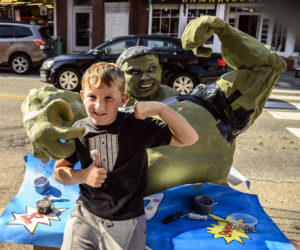 Brooks Blagdon makes a fist along with the Incredible Hulk pumpkin carved by Jenna Blagdon in Damariscotta on Oct. 8. The 377-pound pumpkin was grown by Pat Denny and sponsored by Barn Door Baking Company. (Bisi Cameron Yee photo)