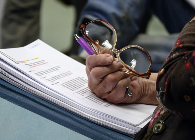 A hand rests on copies of ordinances proposed by the town's planning board  during a board of selectmen's meeting in Jefferson on Oct. 4. The ordinances have been in development for over three years. (Bisi Cameron Yee photo)