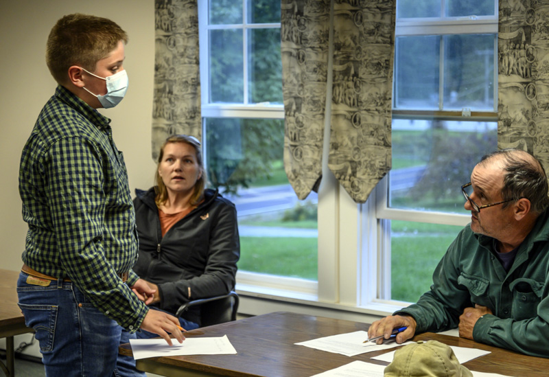Gregory Demeritt, an 8th grader at JVS questions Greg Johnston, chair of the board of selectmen about road maintenance for a school project in Jefferson on Oct. 4. (Bisi Cameron Yee photo)