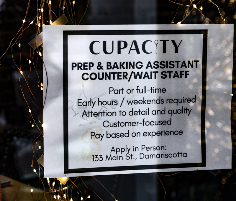 """A """"Now Hiring"""" sign is wreathed by lights in the window of Cupacity in Damariscotta on July 17. (Bisi Cameron Yee photo, LCN file)"""