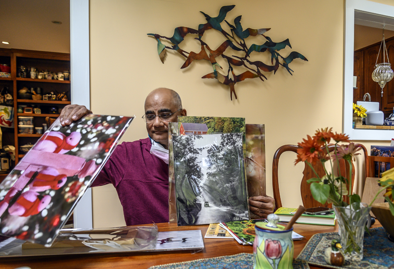 Dr. Rifat Zaidi shuffles through prints in Newcastle on Sept. 30. The photographs will be on display at LincolnHealth's Miles campus starting Oct. 8, and proceeds from the sales will benefit a girls' school in Zaidi's native Pakistan that he has supported since its inception. (Bisi Cameron Yee photo)
