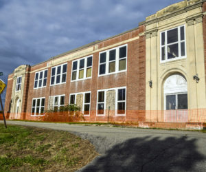 A temporary fence surrounds the A.D. Gray School in Waldoboro on Oct. 18. An engineering report determined that the brick facade is not attached to the front of the building and there is a risk that bricks could fall. (Bisi Cameron Yee photo)