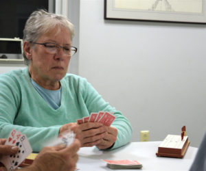Ruth Gilbert looks intently at her cards as she contemplates which one to toss to the crib at the Wiscasset Senior Center on Sept. 30. (Nate Poole photo)